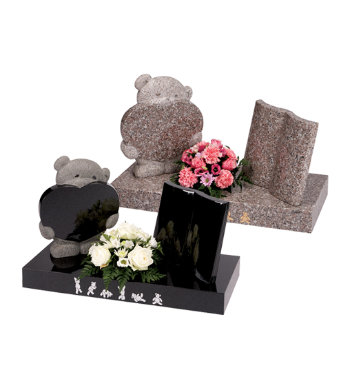 Black granite children's headstone with small carved teddy bear with heart and book.