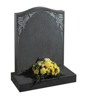 Honed south african dark grey granite gravestone with carved floral design.