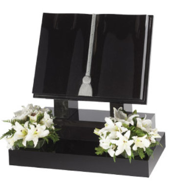 Black granite book shaped headstone with fully carved book, natural tassel on raised base.