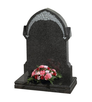 South African dark grey granite headstone of gothic shape with floral carving.