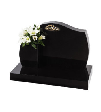 Black granite headstone with barrel sides and accompanying vase.